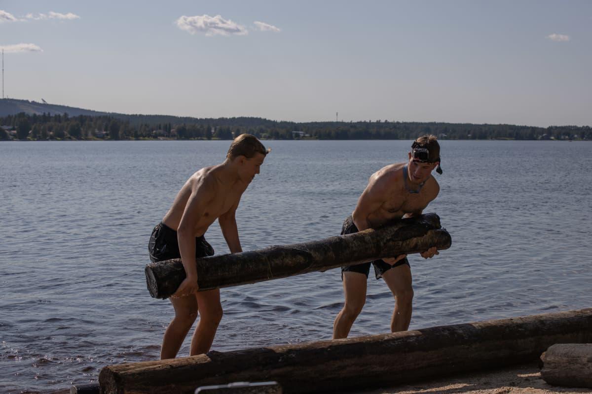 Uppotukkia kannetaan järvestä rannalle.