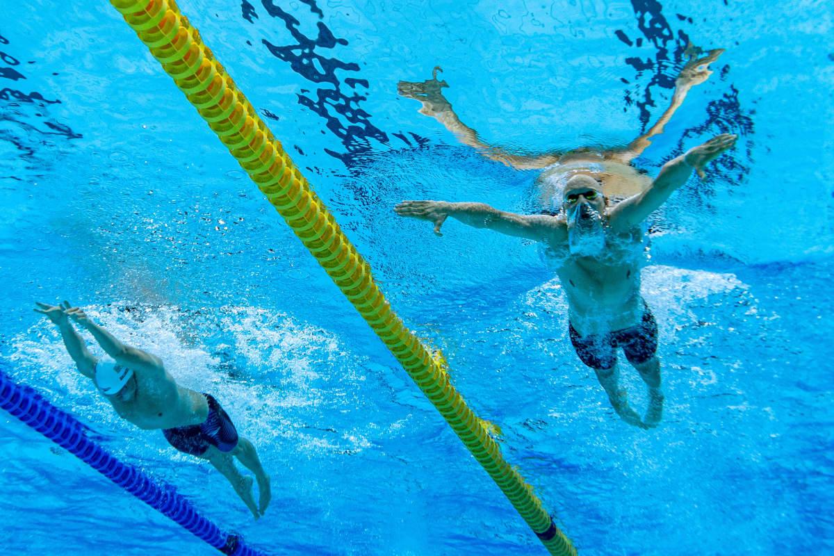 Matti Mattsson kuvattuna alhaalta päin uima-altaassa. Mattssonin pää on veden alla ja kädet kauhovat vettä.