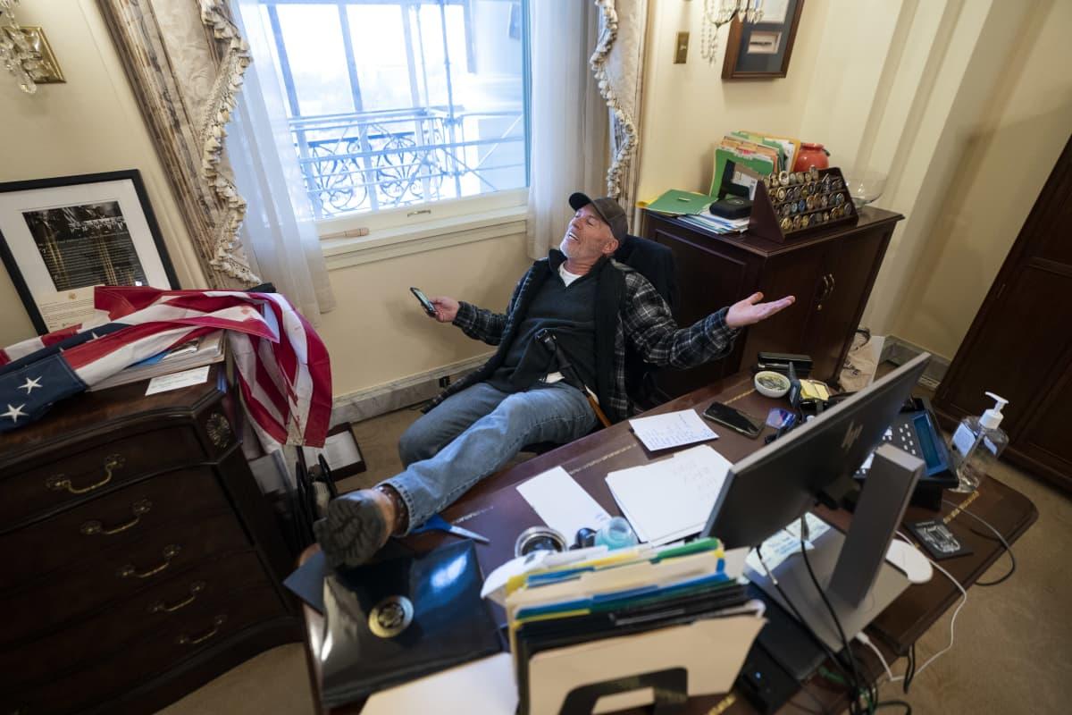 Mies istuu Pelosin työhuoneessa jalka pöydällä.