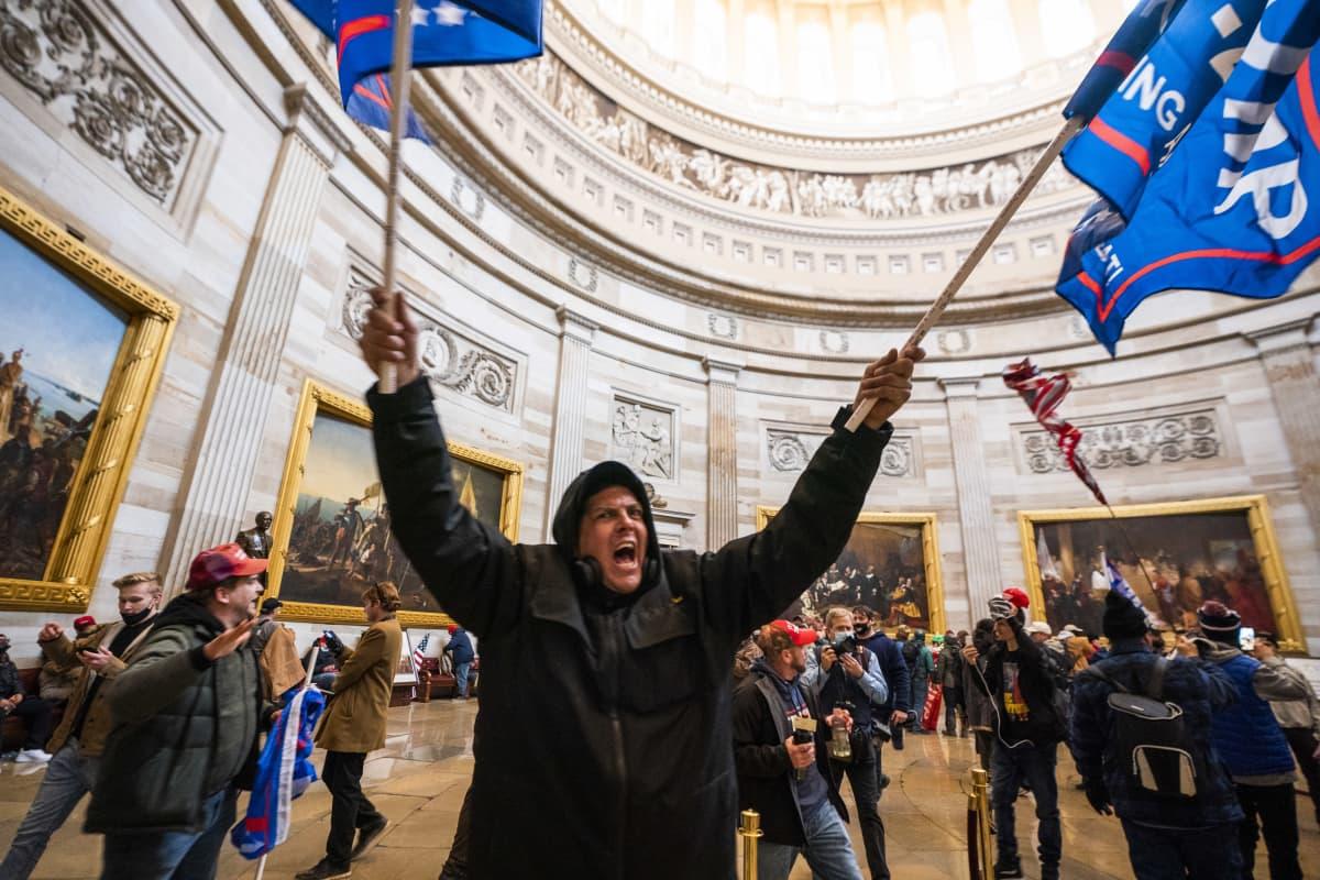 Mies heiluttaa lippuja kongressin valtaajien keskellä.