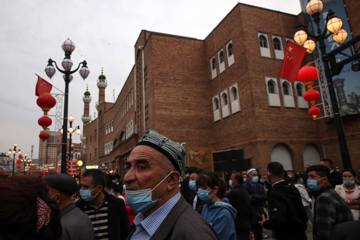 Uiguuri mies seisoo väkijoukossa Xinjiangissa, Kiinassa.