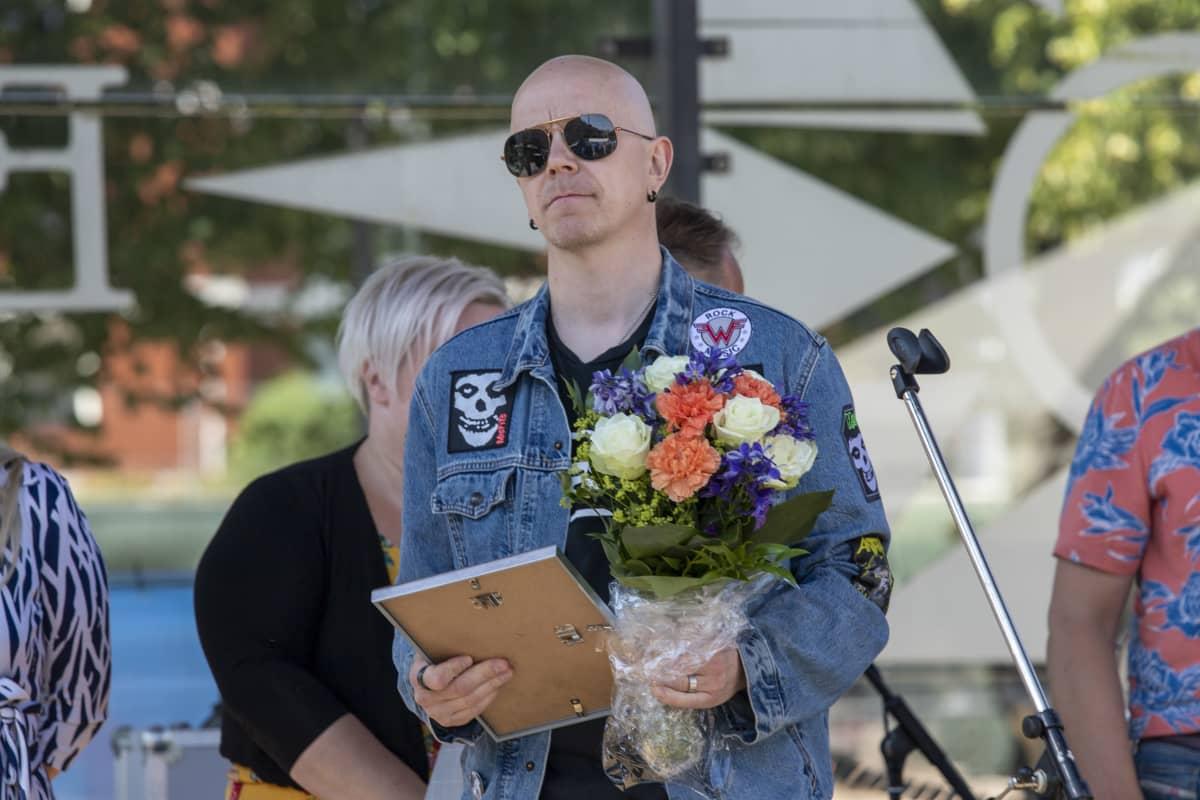 Toni Wirtasella käsissään kunniakirja ja kukkakimppu