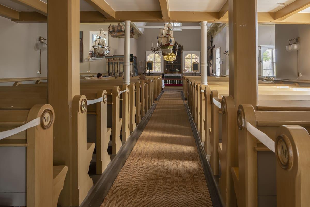 Kustavin kirkon sisäkuva penkkirivien välistä.