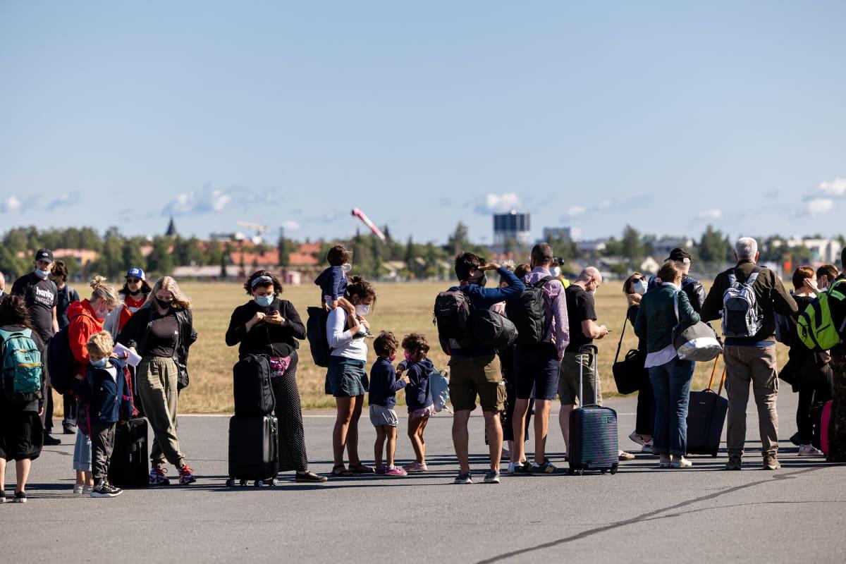 Turisteja odottamassa laukkujaan Lappeenrannan lentoasemalla.