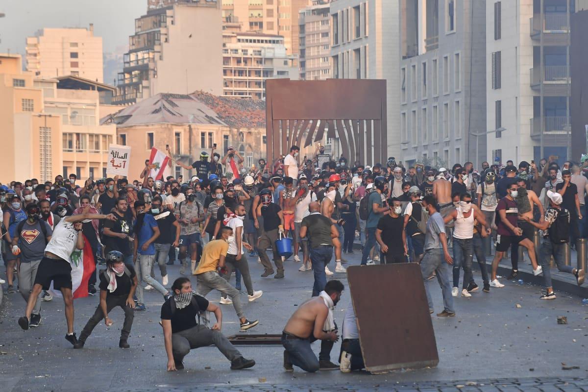 Mielenosoittajat heittävät kiviä.