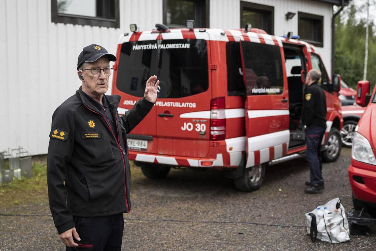 Pelastusjohtaja Jarmo Haapanen taustallaan päivystävän palomestarin auto.