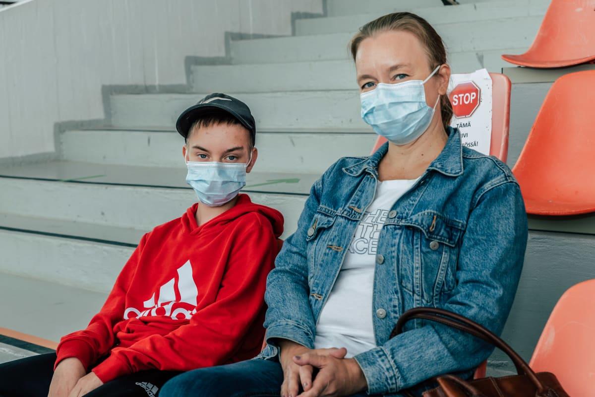 Otso Sokka ja äitinsä istuu odottamassa Killerin raviradan katsomon penkeillä rokotteen ottamisen jälkeen.