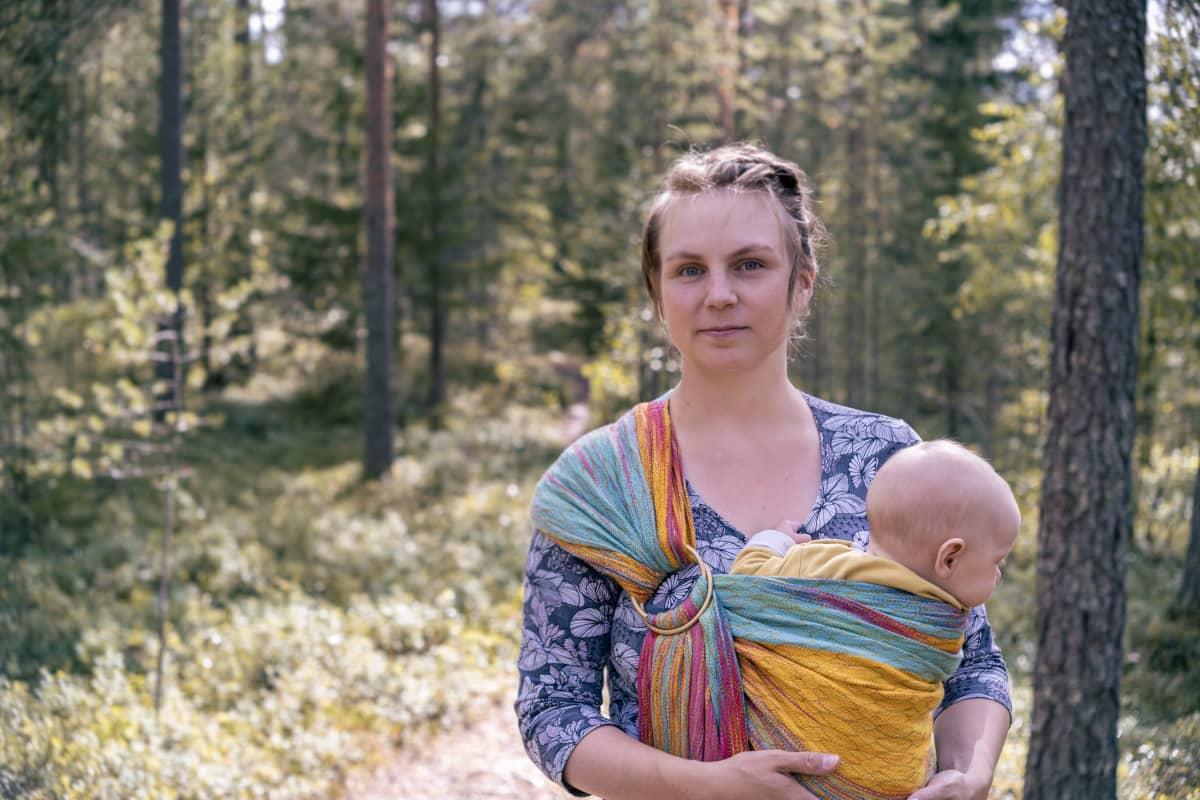 Katariina Kuvaja seisoo metsässä ja pitelee vauvaa sylissään kantokopassa.