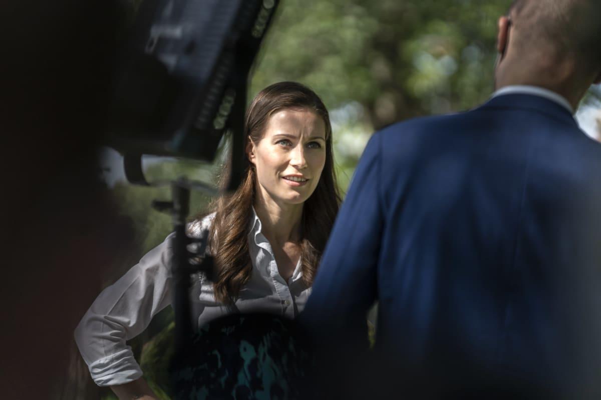 Pääministeri Sanna Marin juttelee Yle uutisten politiikan toimittaja Ari Hakahuhdan kanssa ennen haastattelua Kesärannan pihassa.
