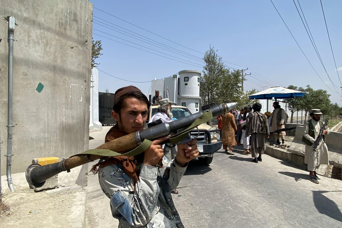 Taliban-sotilas pitää raketinheitintä kädessään Afganistanin sisäministeriön edessä Kabulissa.
