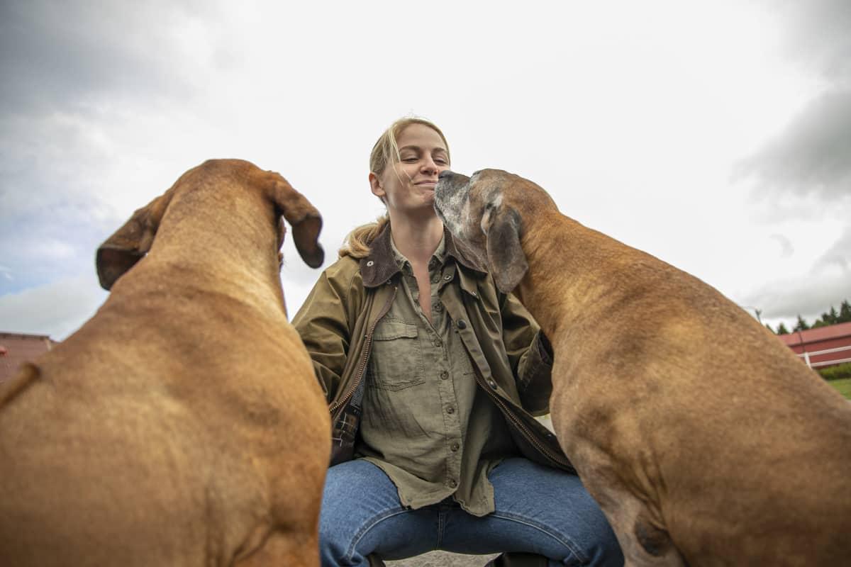 Suontaan kartanon emäntä Ellen Rydbeck koiriensa kanssa kartanon piha-alueella.