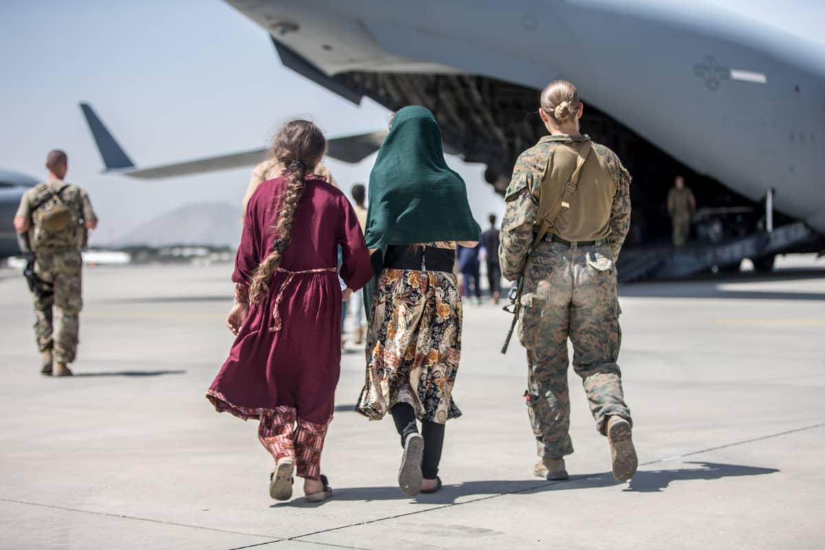 Två civila personer går mot ett flygplan på Kabuls flygplats. Bredvid dem en soldat. I bakgrunden syns ännu en soldat.