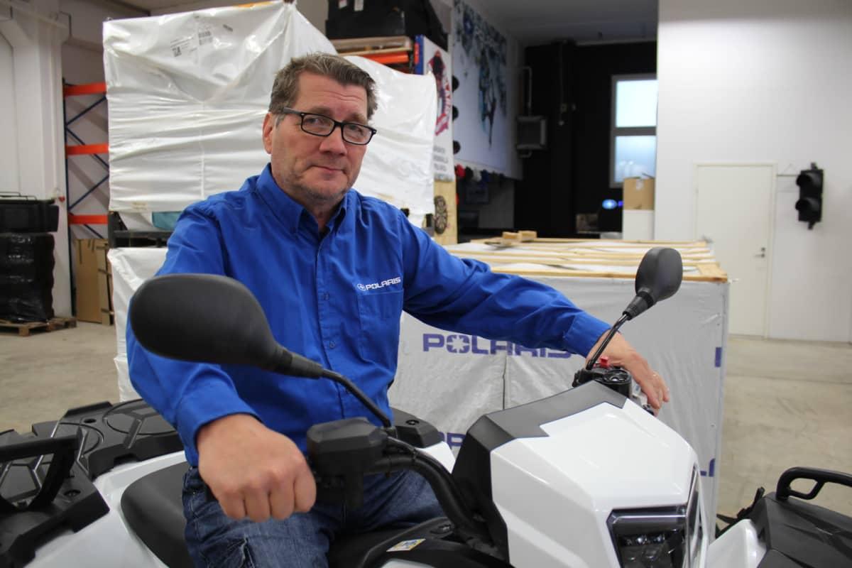Polaris Finlandin toimitusjohtaja Jyrki Tikkanen istuu traktorimönkijän istuu valken trakorimönkijän satulassa.