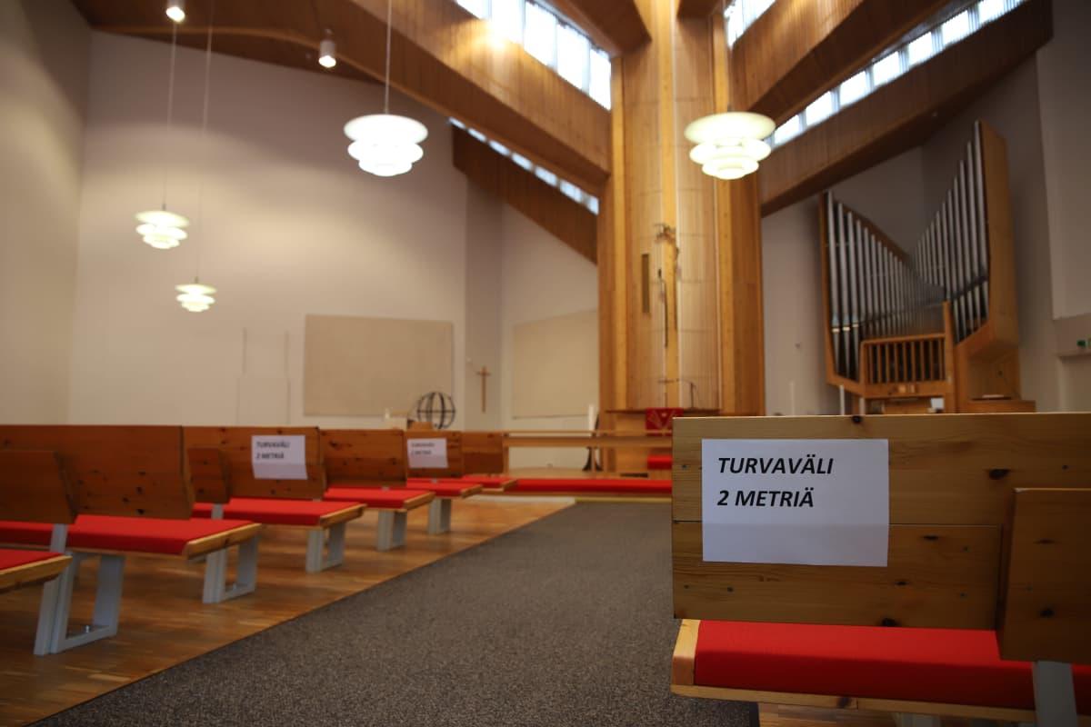 Tyhjä kirkkosali Rovaniemen kirkosta, penkissä kyltti 2 metrin turvavälistä.
