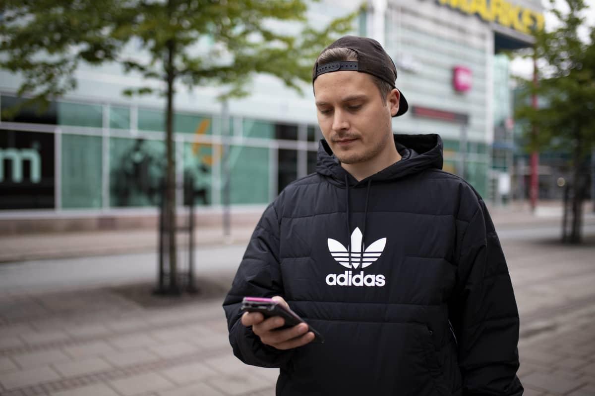 Joni Parviainen seisoo kävelykadulla ja näppäilee kännykkäänsä.