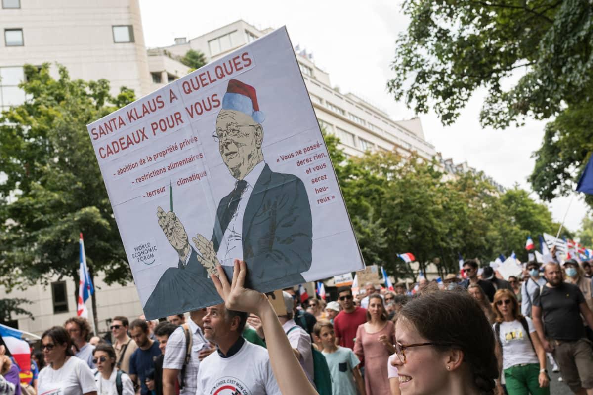 Mielenosoittaja kantaa kulkueessa kylttiä, jossa on Maailman talousfoorumin puheenjohtajan Klaus Scwabin kuva.