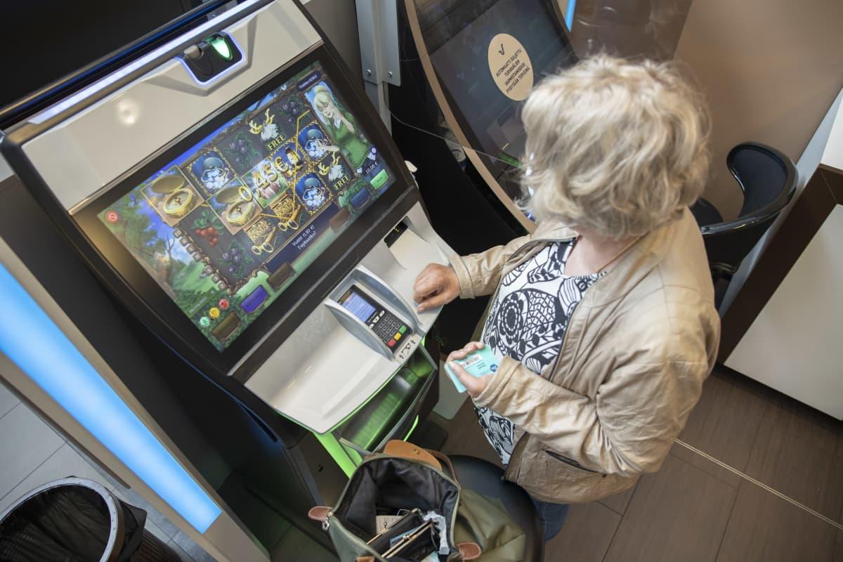 Eläkeläisnainen pelaa rahapeliä. Kädessä veikkauskortti.