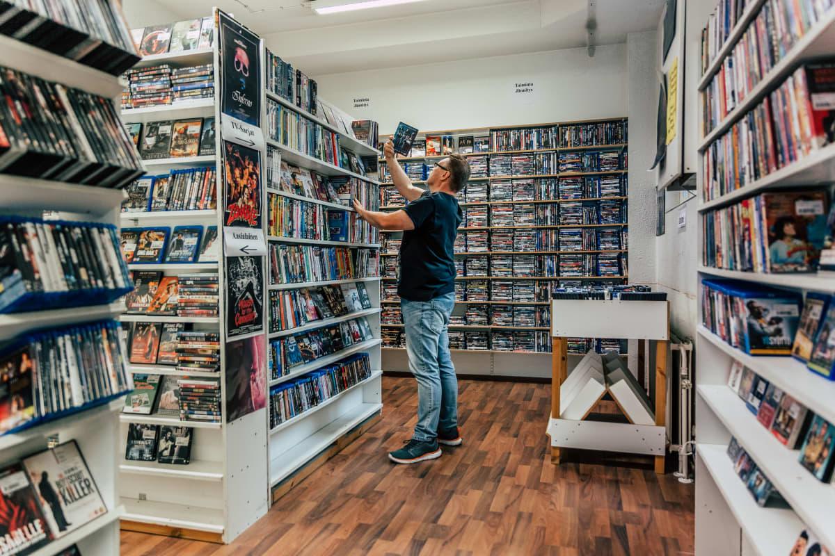 Mika Venäläinen laittaa Dvd-elokuvaa hyllyyn.