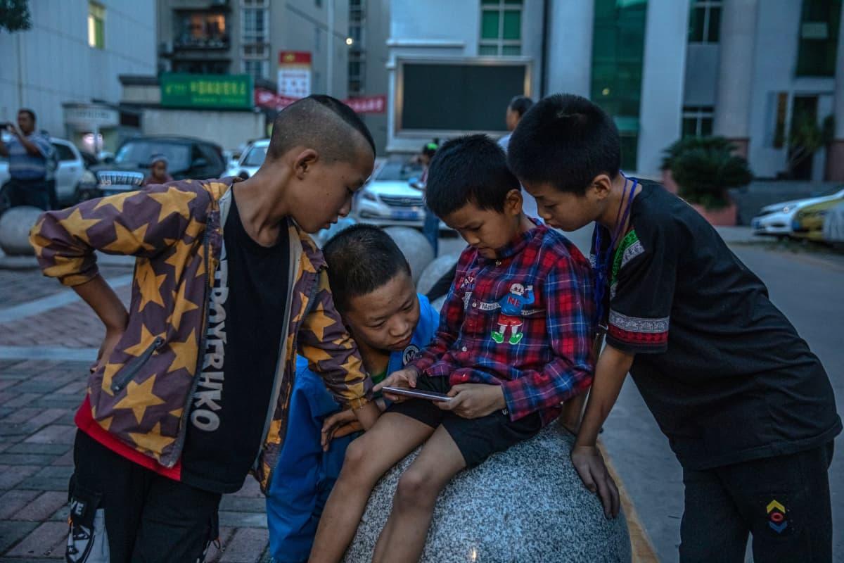 Kiinalaiset pojat tuijottavat puhelinta.