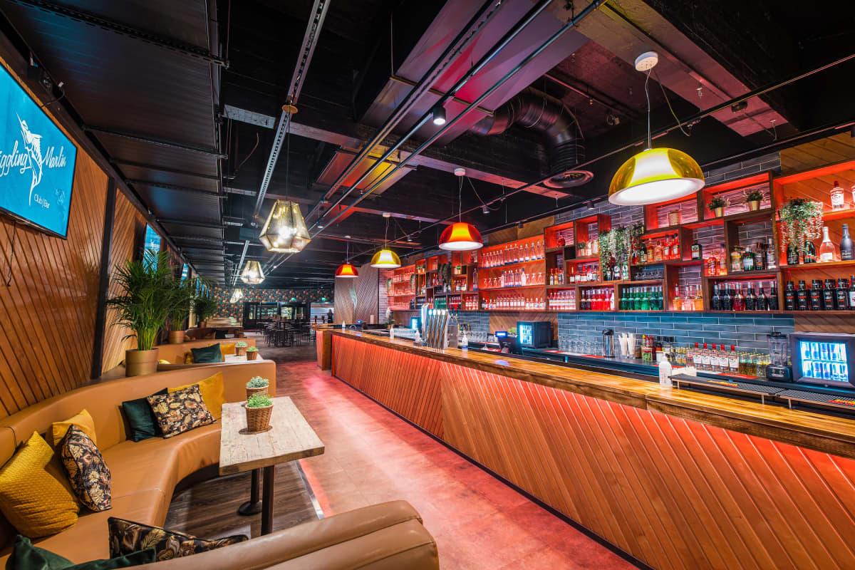 Pitkä ravintolan tiski, jonka edessä sohvaryhmiä ja taustalla viinapulloja hyllyllä.