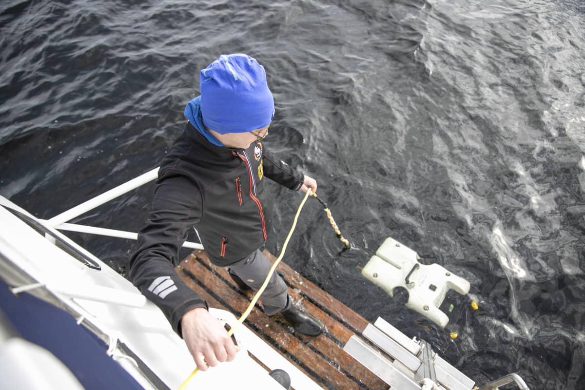 Sukeltaja Mikko Suutari laskee sukellusrobottia veteen.