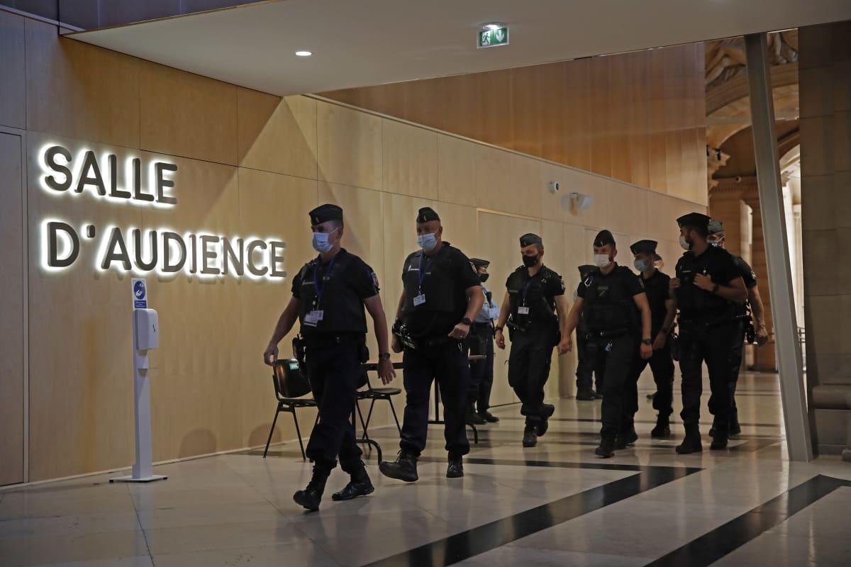Poliiseja Pariisin oikeustalossa. Oikeudenkäynti Pariisin 2015 terrori-iskuista alkaa vankkojen turvatoimien säestämänä.