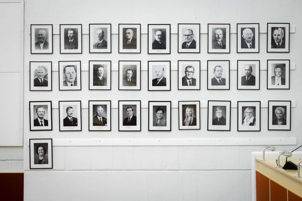 Kaupunginhallituksen puheenjohtajien valokuva Viitasaaren kunnantalon valtuustosalin seinällä.