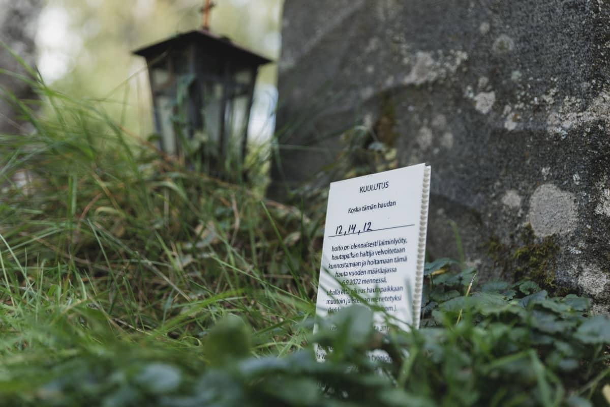 Hautakiven edessä levy jossa lukee: Kuulutus, tämän haudan hoito on olennaisesti laiminlyötyoito. Hautapaikan haltia velvoitetaan kunnostamaan ja hoitamaan tämä hauta...