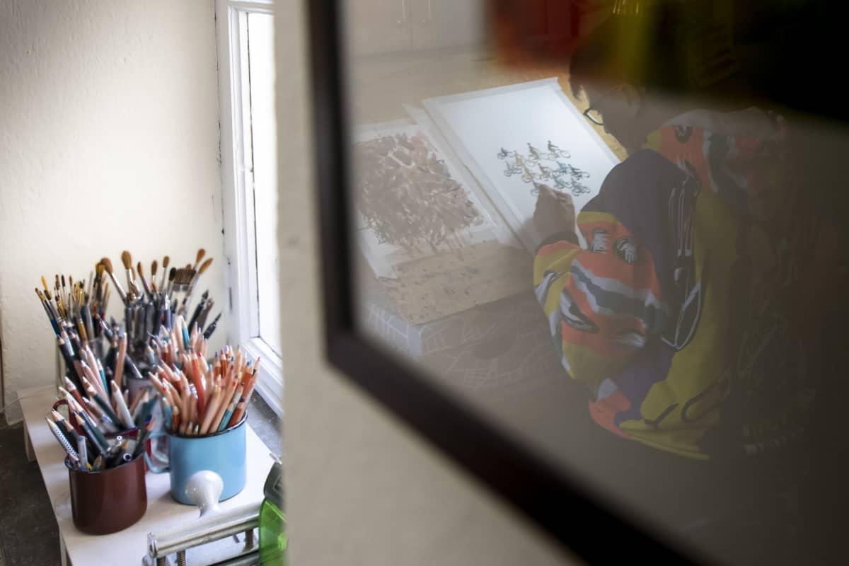 Sarjakuvataiteilija Tiitu Takalon kuva heijastuu seinällä olevan taulun lasista.