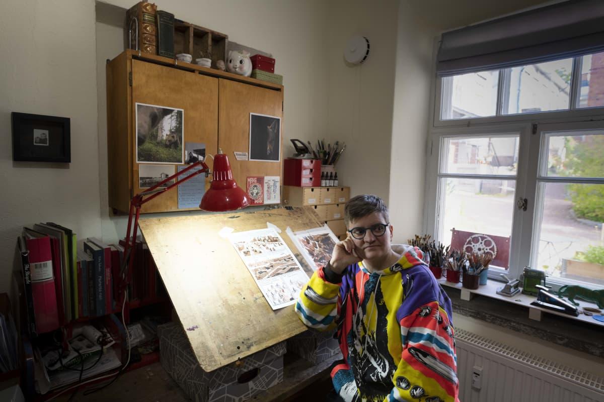 Sarjakuvataiteilija Tiitu Takalo työhuoneessaan piirustuslaudan äärellä.