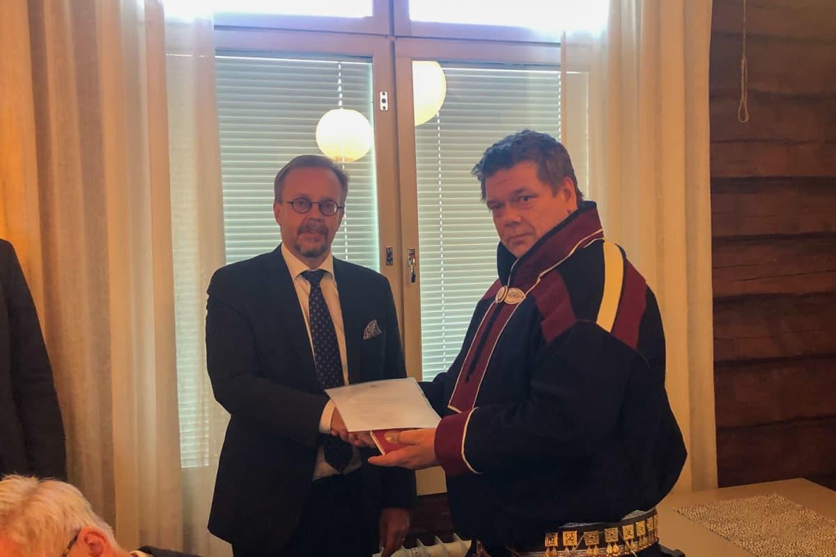 Korkeimman hallinto-oikeuden presidentti Tatu Leppänen ojentaa kunniamitalin Saamelaiskäräjien II varapuheenjohtaja Leo Aikiolle 9.9.2021.