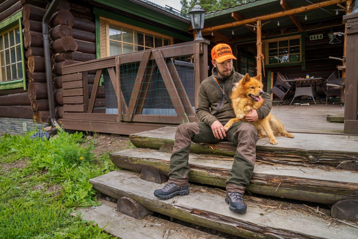 Kyösti Husu ja Äijä-koira hirsitalon portailla.