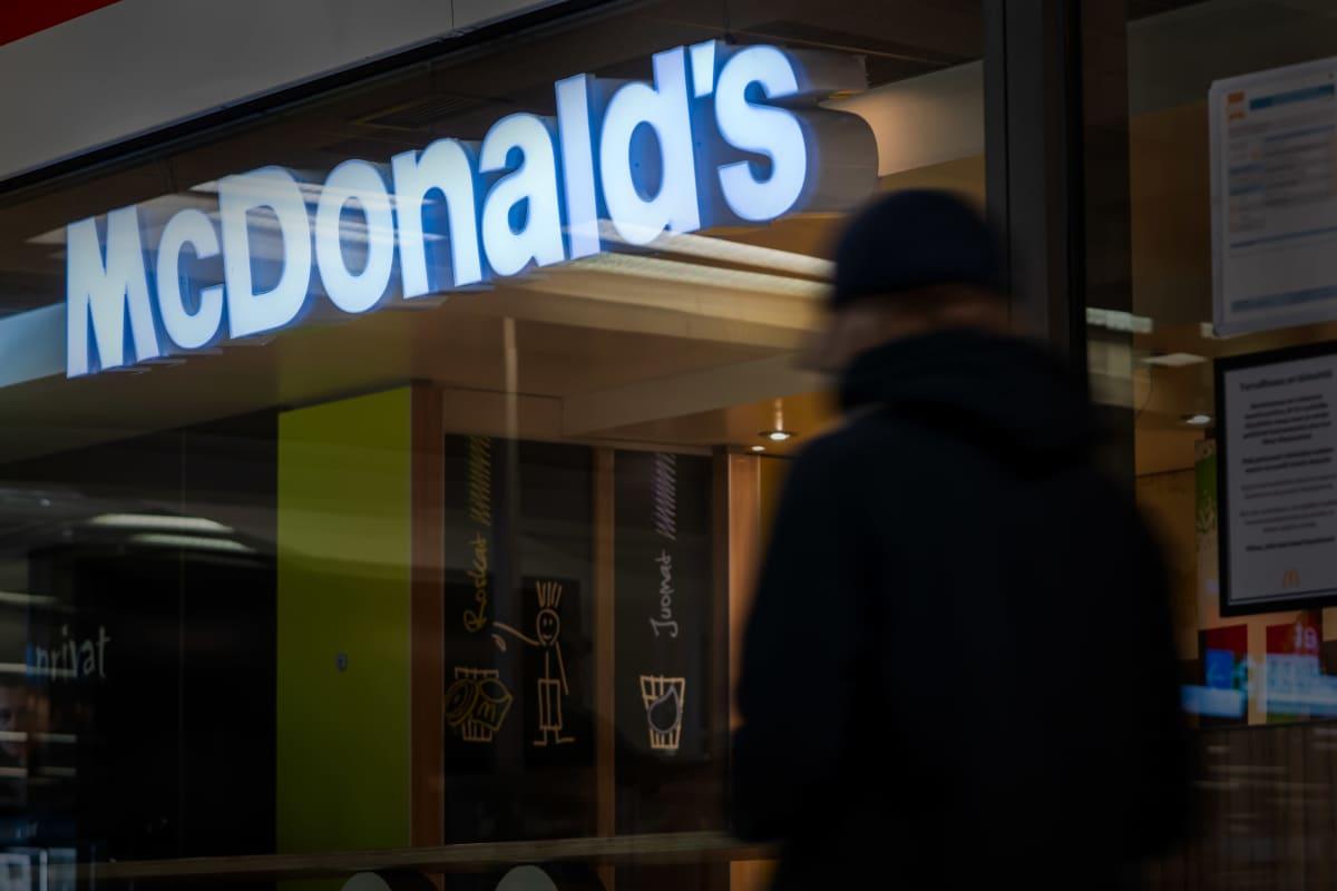 Nuori kävelee McDonalds's mainoskyltin alta.