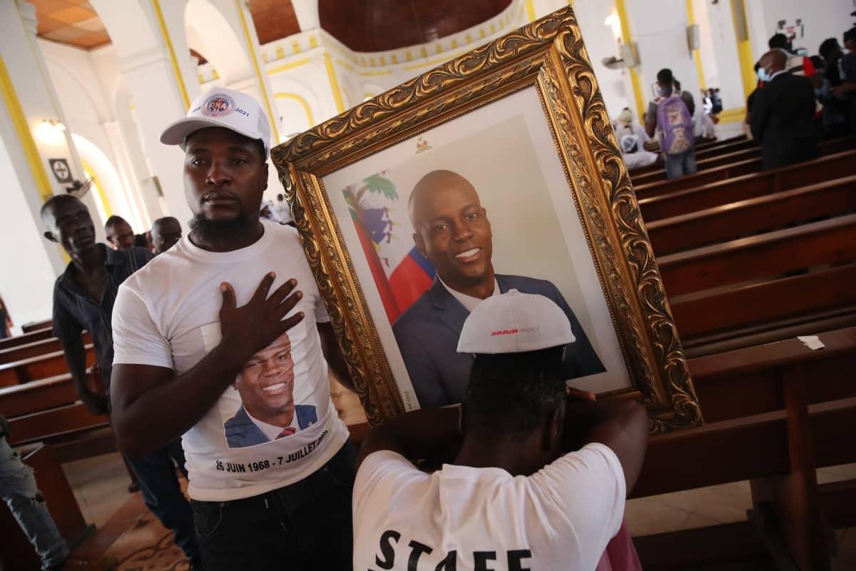 Mies pitelee kirkossa presidentti Jovenel Moisea esittävää taulua. Presidentin kuva on myös hänen paidassaan. Toinen mies nojaa päätään käsiinsä.