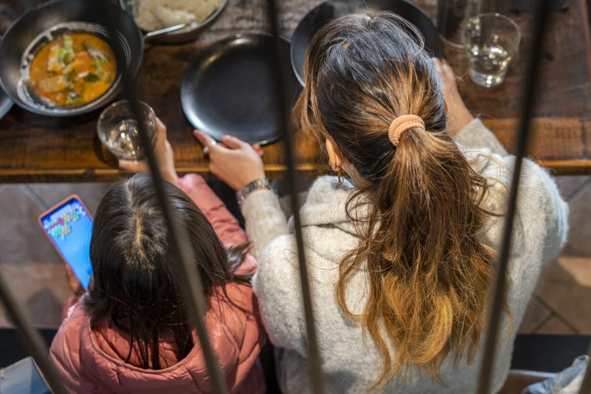 Anonyymisti kuvattu afgaaninainen ja lapsi ravintolassa