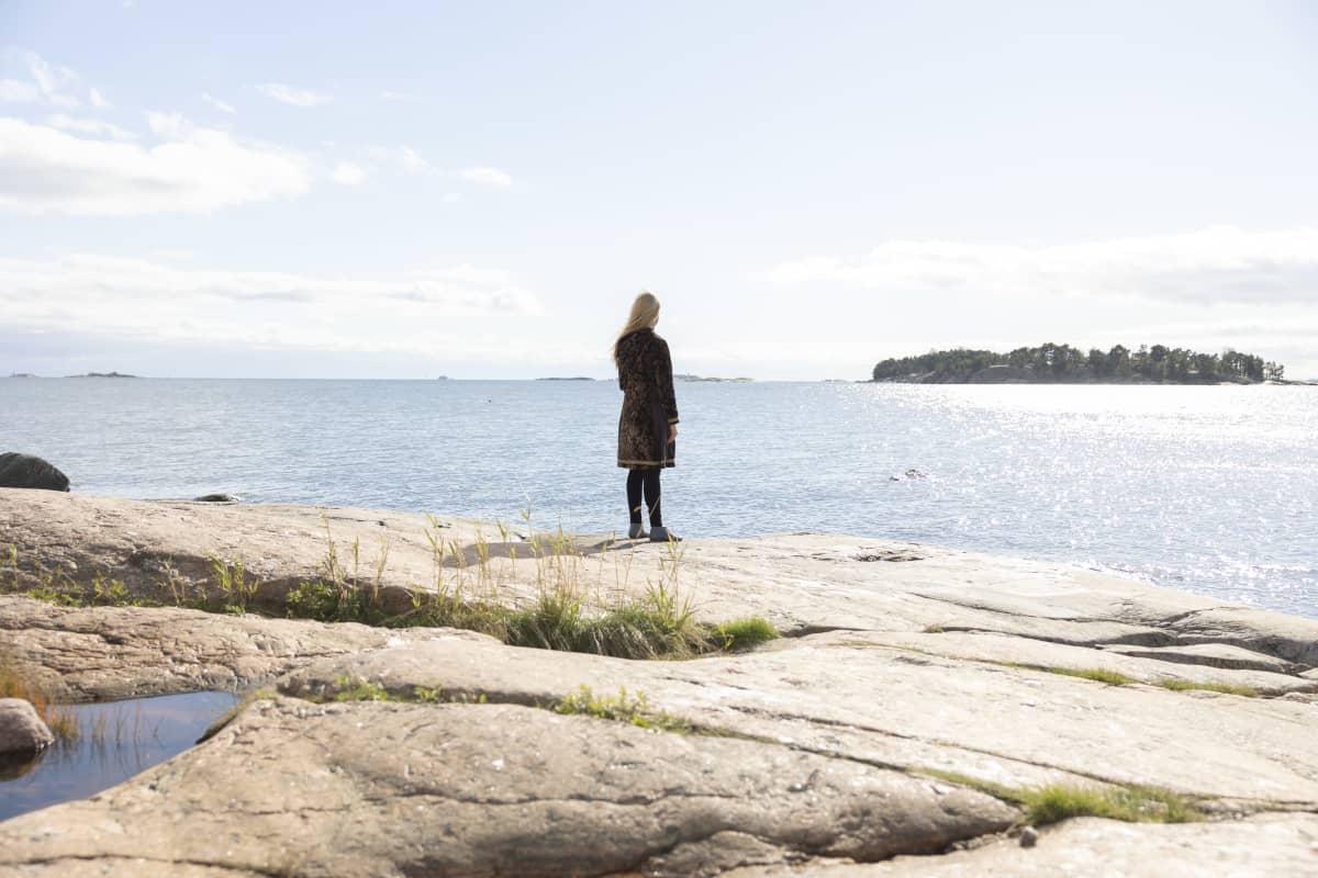 Johanna Venho seisoo meren rannalla.