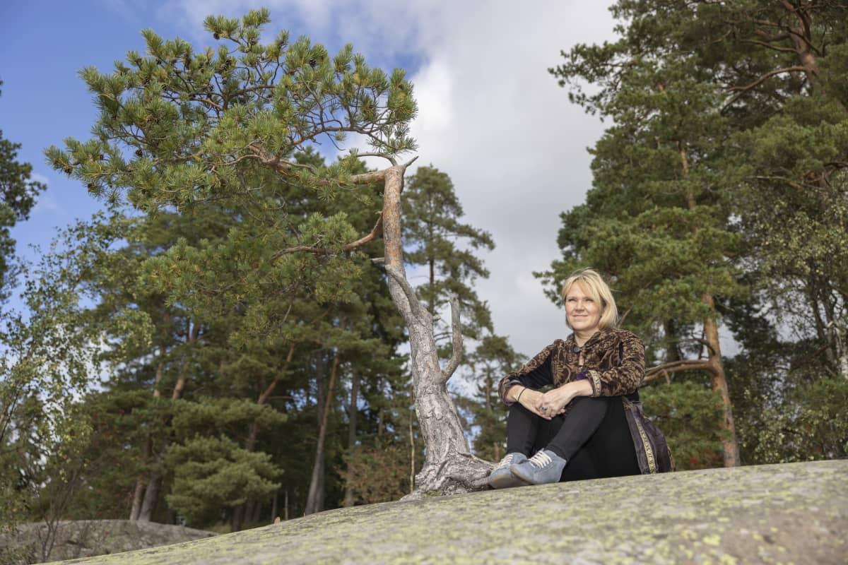 Kirjailija Johanna Venho istuu kalliolla. Vieressä pieni mänty.
