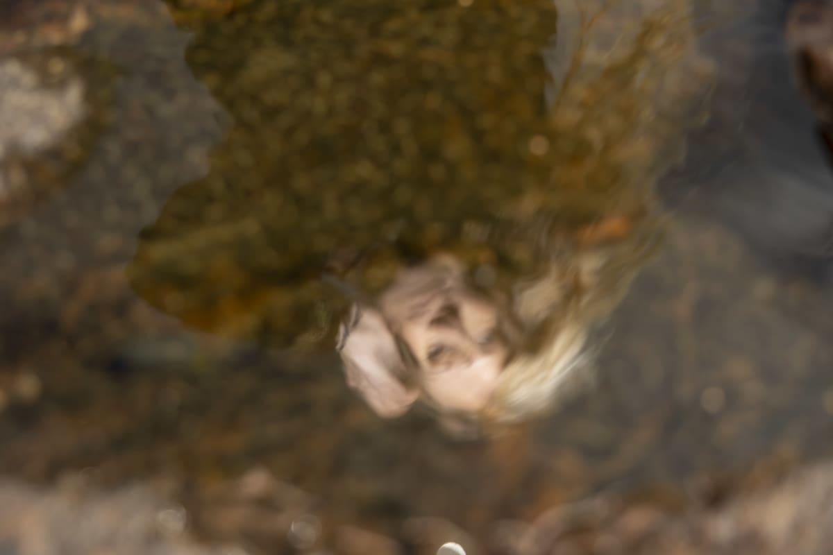 Kirjailija Johanna Venhon kasvot heijastuvat  vedestä.