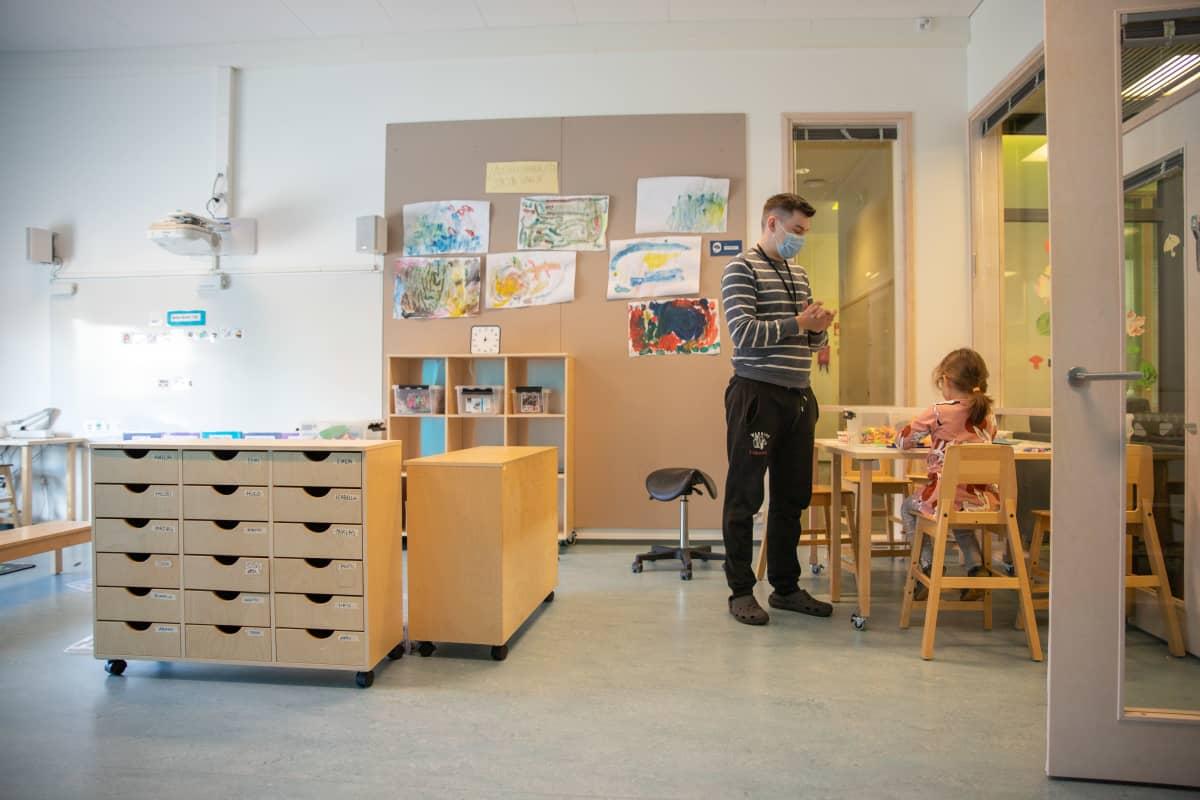 Päiväkodin työntekijä ohjeistaa lasta joka istuu pöydän ääressä.