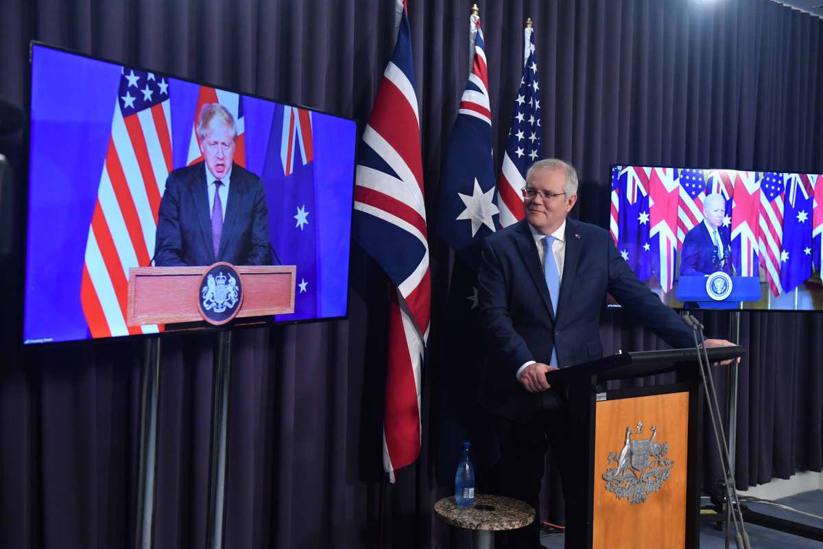 Scott Morrison tiedotustilaisuudessa, taustalla videoyhteydellä Joe Biden ja Boris Johnson