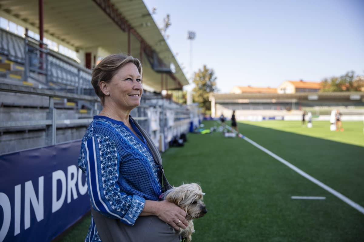 naisella on koira sylissään ja hän seisoo jalkapallokentän laidalla
