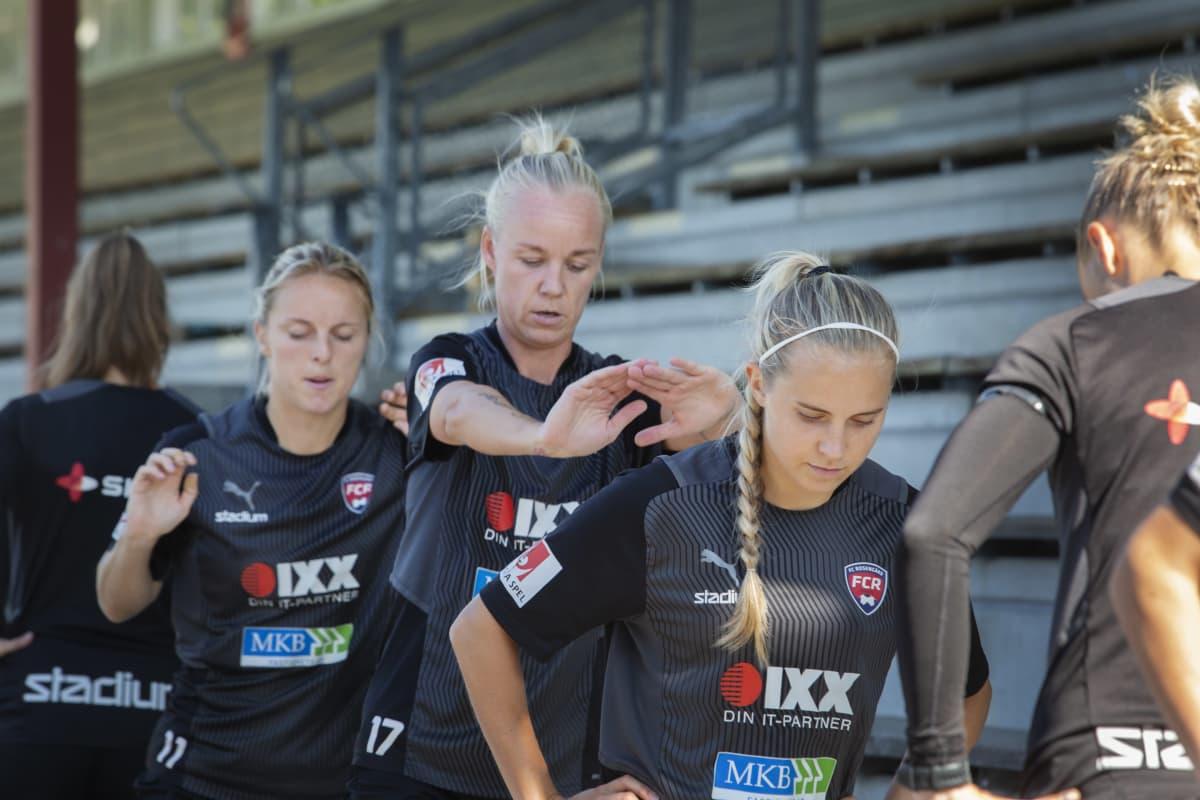 naisjalkapalloilijat seisovat rivissä ja harjoittelevat