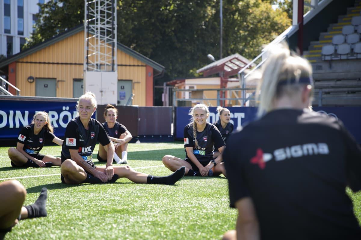 naisjalkapalloilijat venyttelevät nurmella