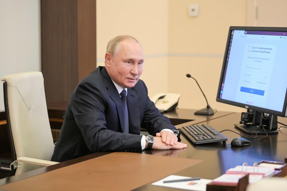 Putin istuu tummanharmaassa puvussa ja sinisessä kravatissa pöydän ääressä. Pöydällä näkyy mikrofoni ja tietokoneen ruutu.. Putin pitää käsiään päällekkäin pöydällä.