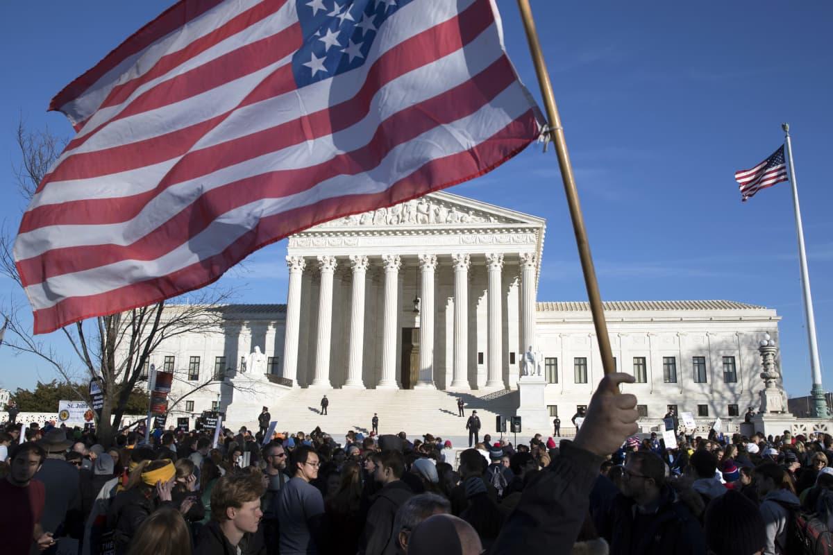 Mielenosoittajia aurinkoisena päivänä Yhdysvaltain korkeimman oikeuden rakennuksen edessä. Keskellä mies heiluttaa suurta Yhdysvaltain lippua.