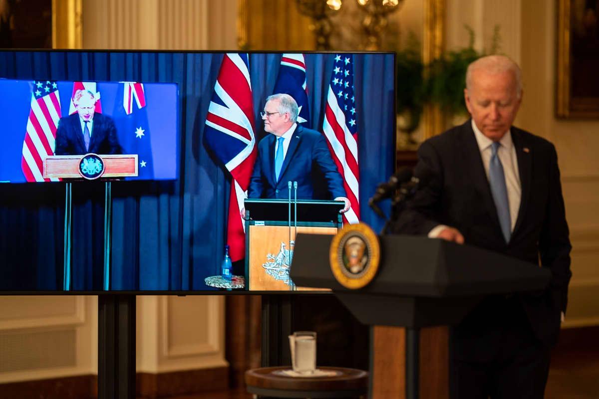 Joe Biden on puhujanpallilla, taustalla Scott Morrison ja Boris Johnson osallistuvat ruuduilla etäyhteyden kautta tilaisuuteen.
