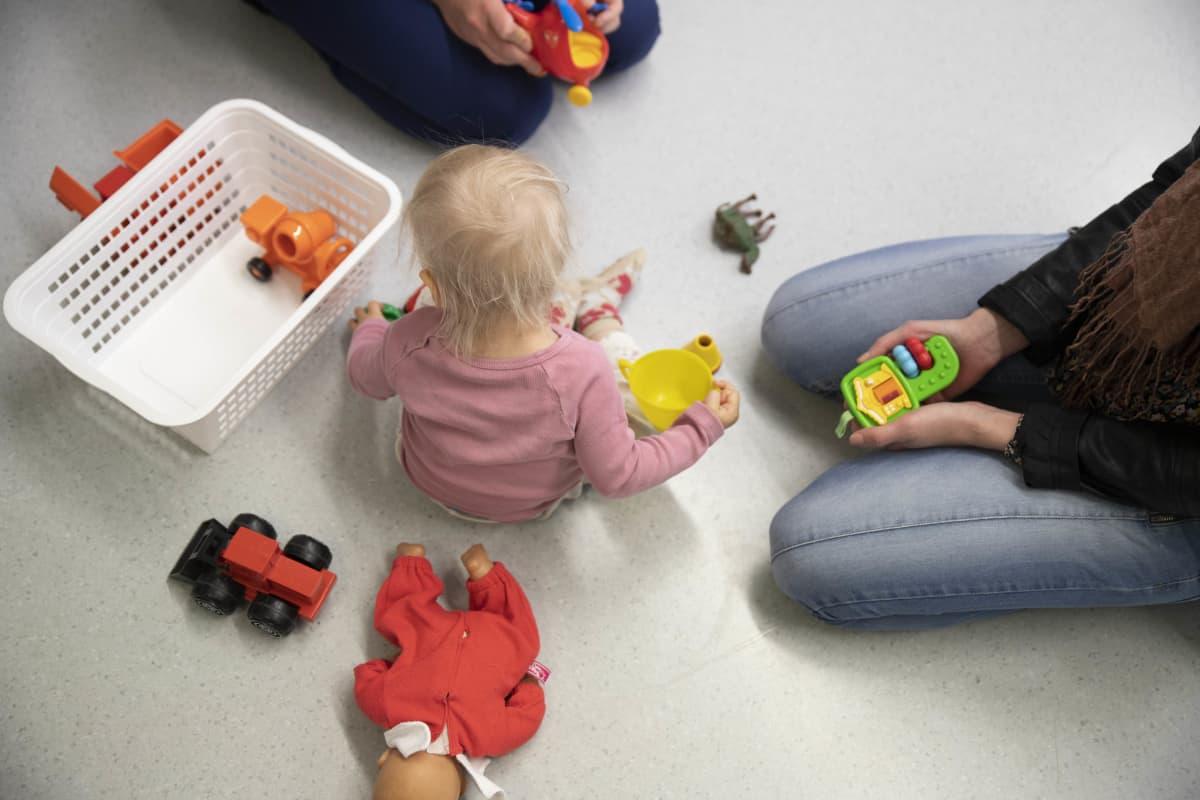 Lapsi leikkii lattialla.