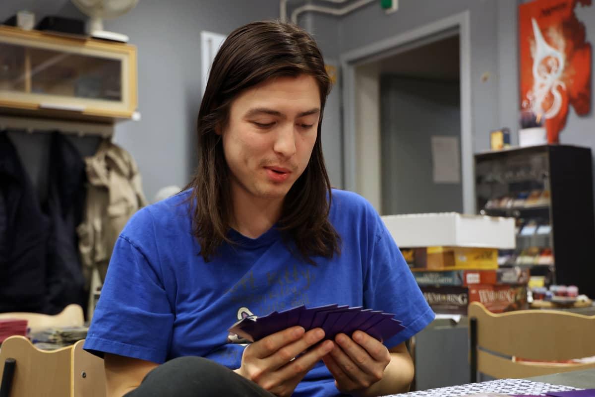 Christian Tuomi pelaa Pokémon-korteilla pöydän ääressä.