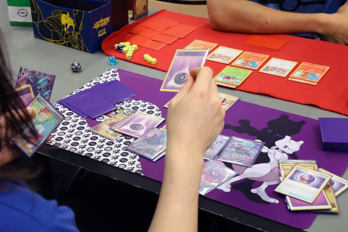 Pokémon-korttipelin pelaamista pöydän ääressä.