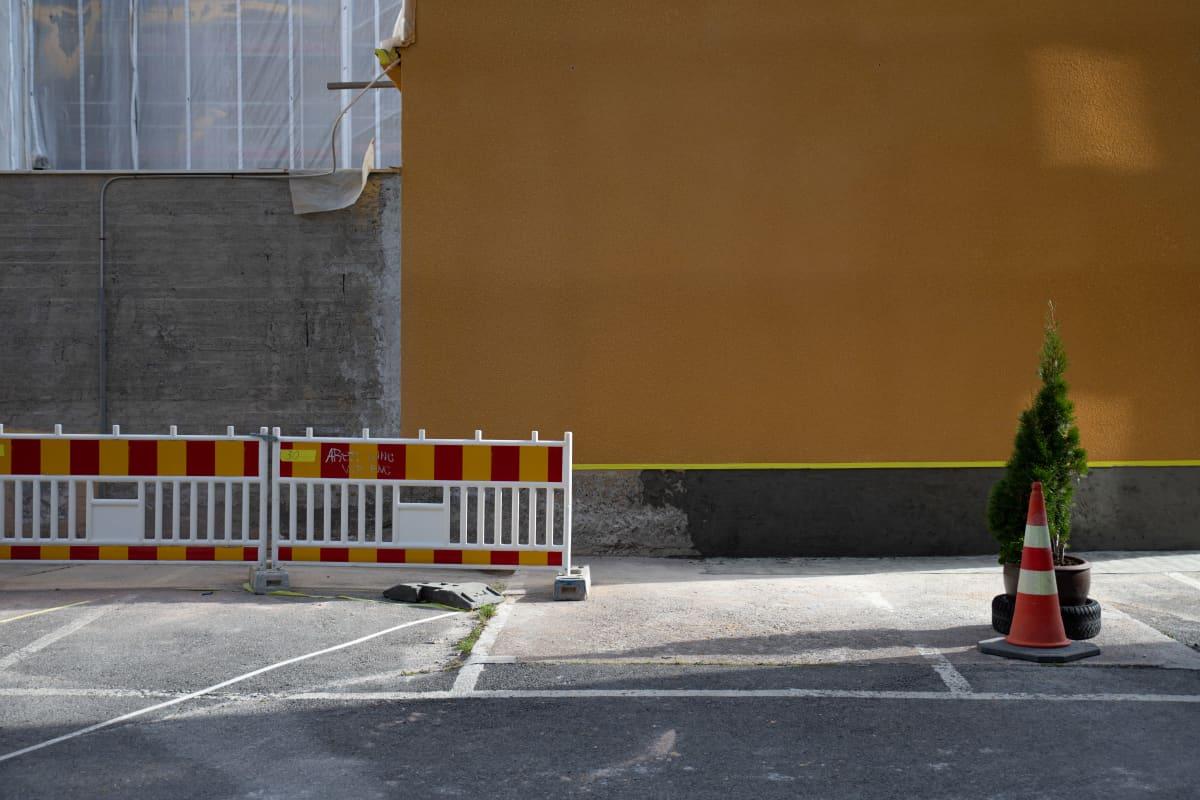 Rakennustyömaan eristysaidat vasemmalla laidalla, keltaisen seinän edessä oikealla yksi pieni puu ja liikenne tötterö.